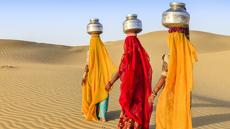 Indian women crossing sand dunes and carrying on their heads water from local well, Thar Desert, Rajasthan, India. Rajasthani women and children often walk long distances through the desert to bring back jugs of water that they carry on their heads. ©iStock.com/Bartosz Hadyniak